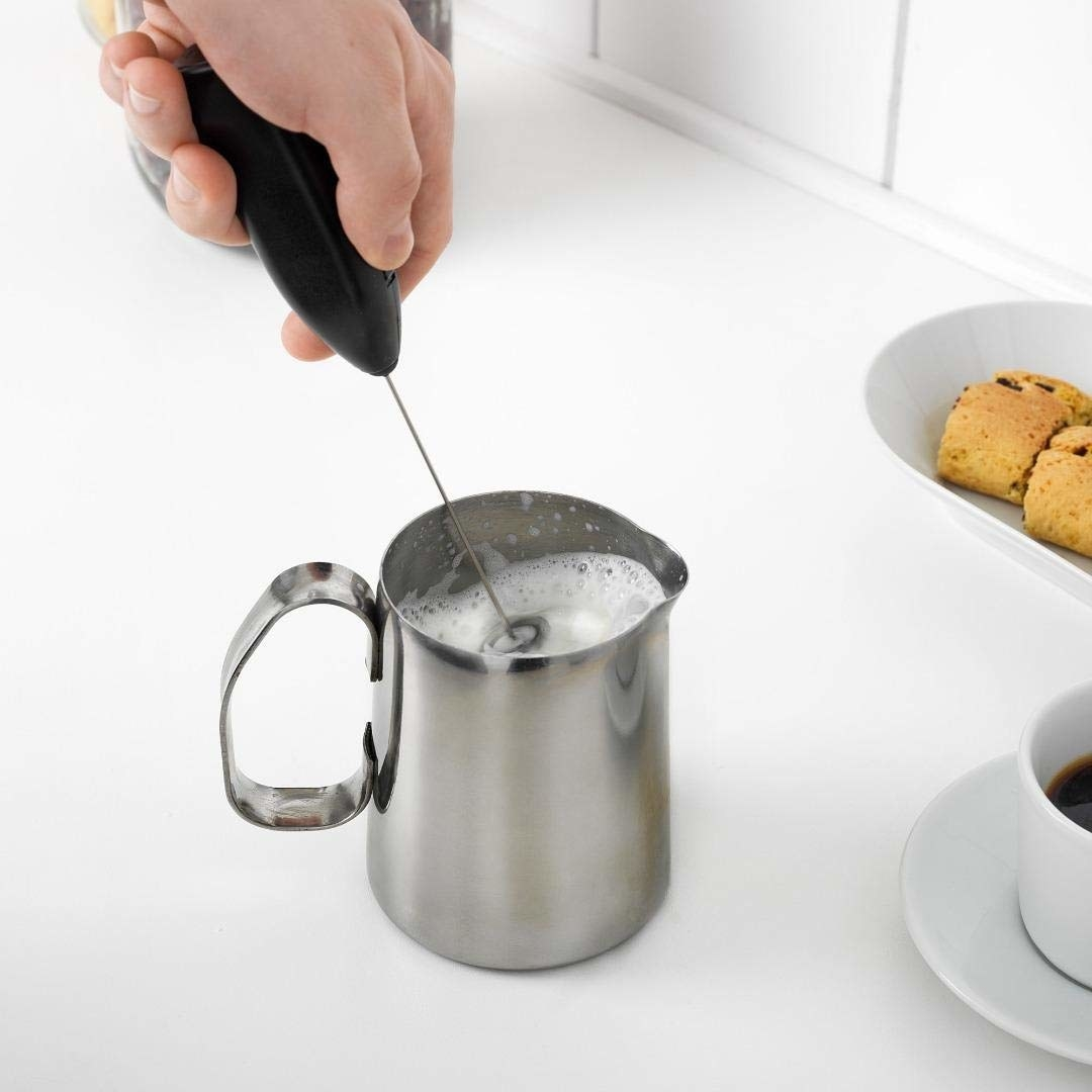 A person frothing milk with the device
