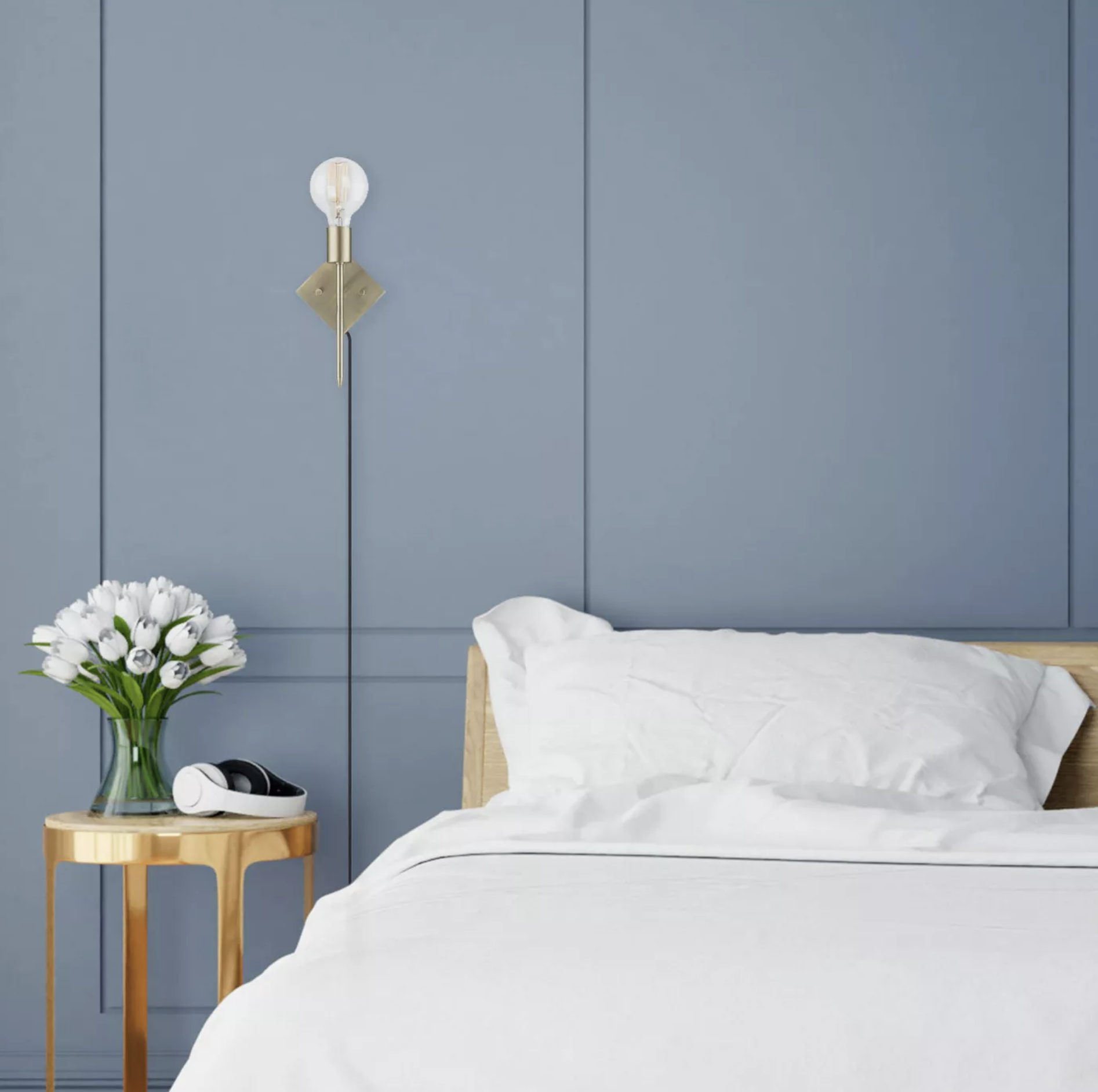 A bedroom with the wall sconce