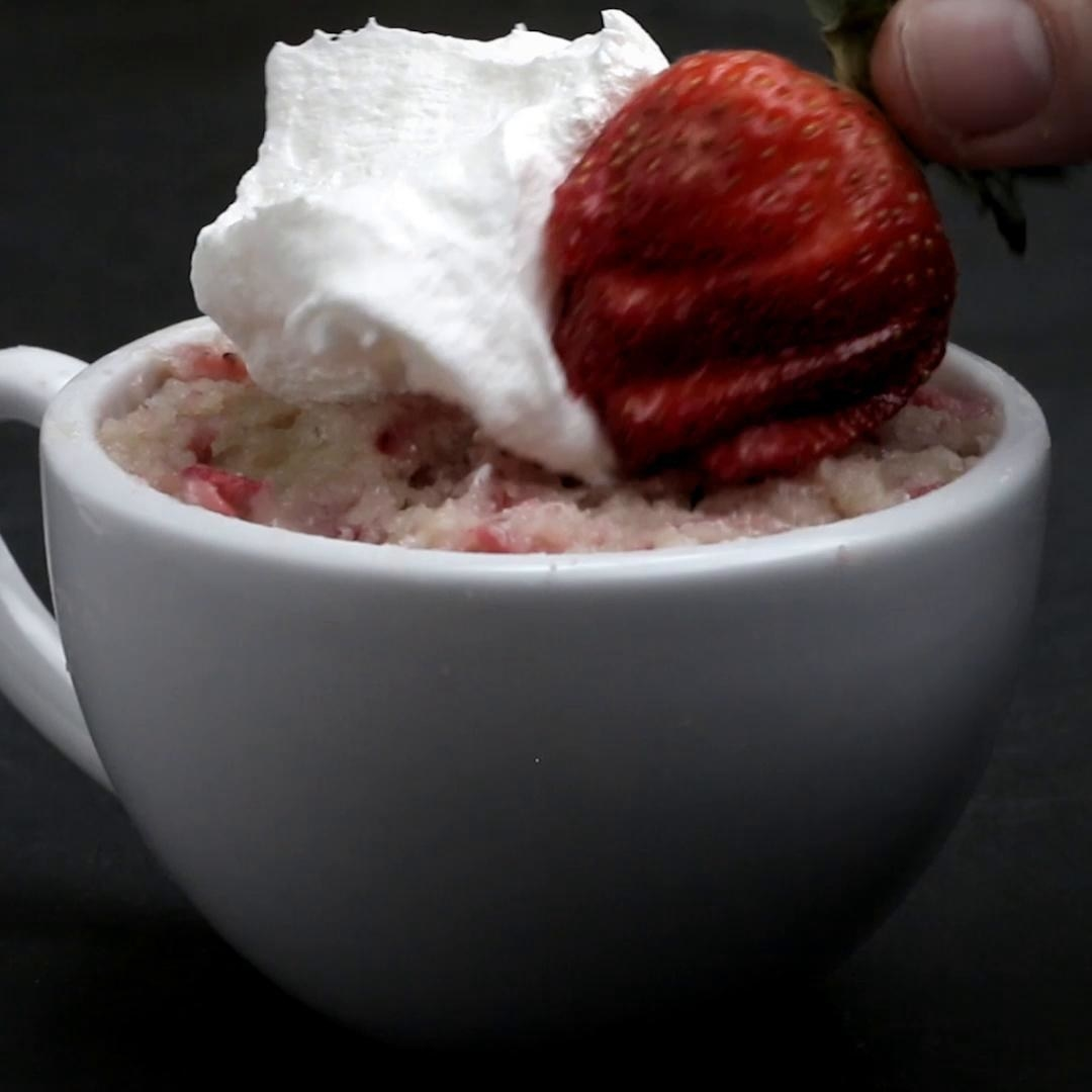 The mug cake topped with whipped cream and a strawberry