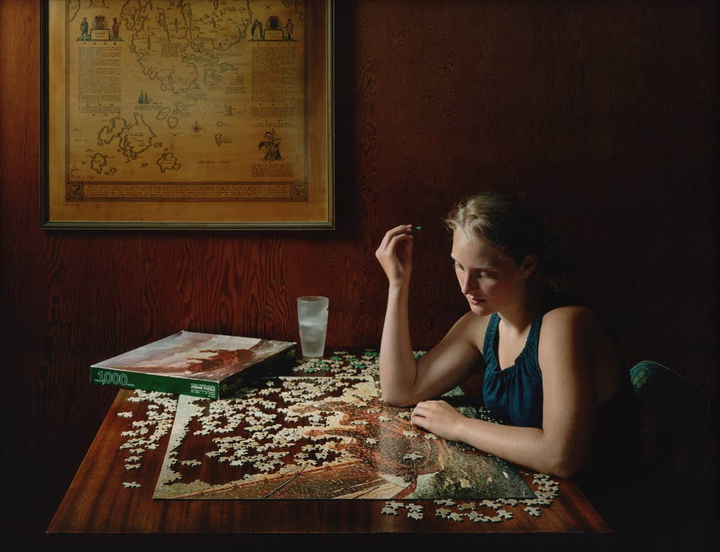 A woman playing with a puzzle in a wooden veneered room