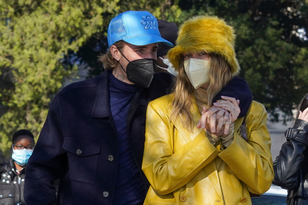 Hailey and Justin walking outside while wearing their face masks