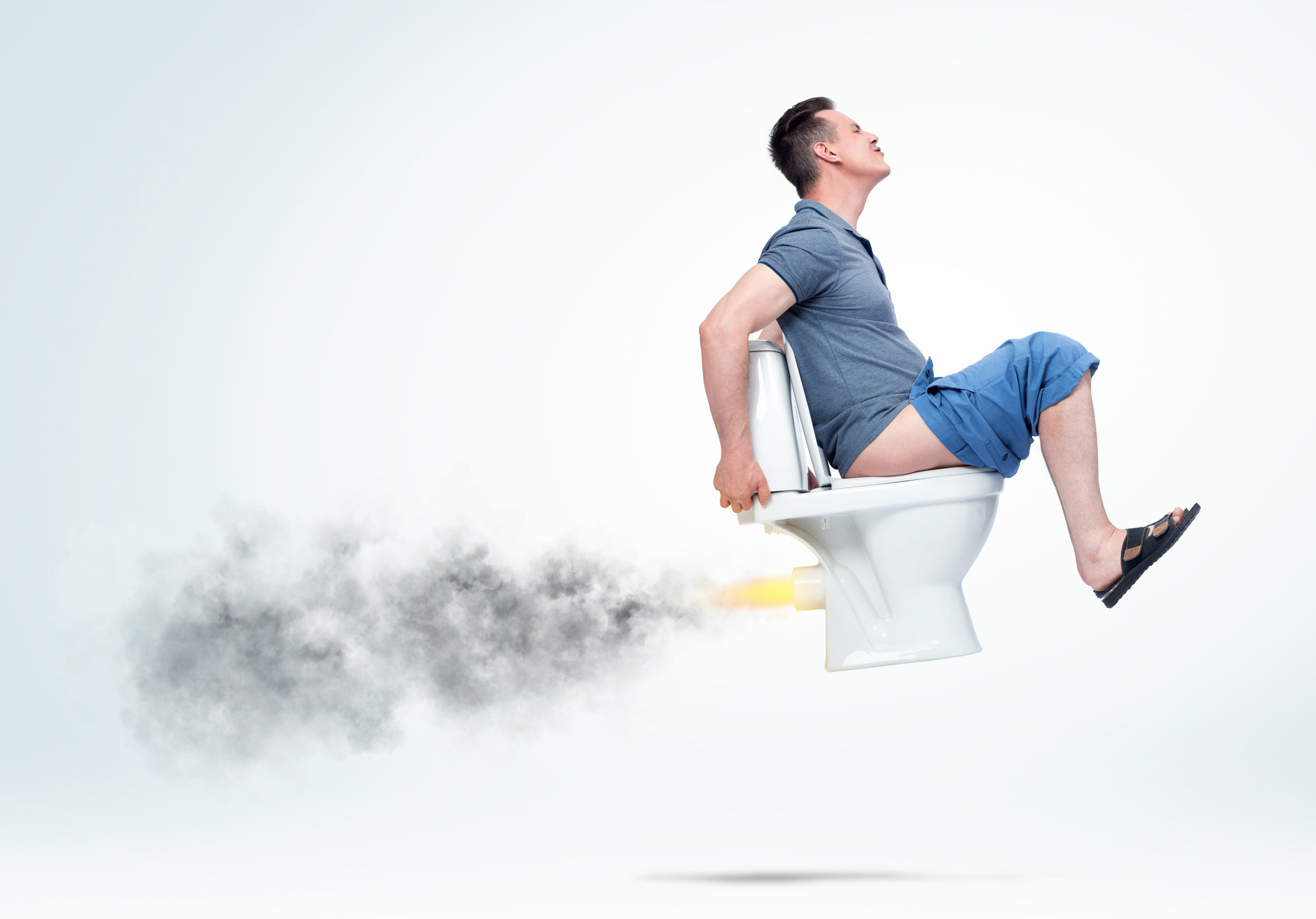 A man sitting on an airborne toilet in discomfort as smoke and fire comes out of the back