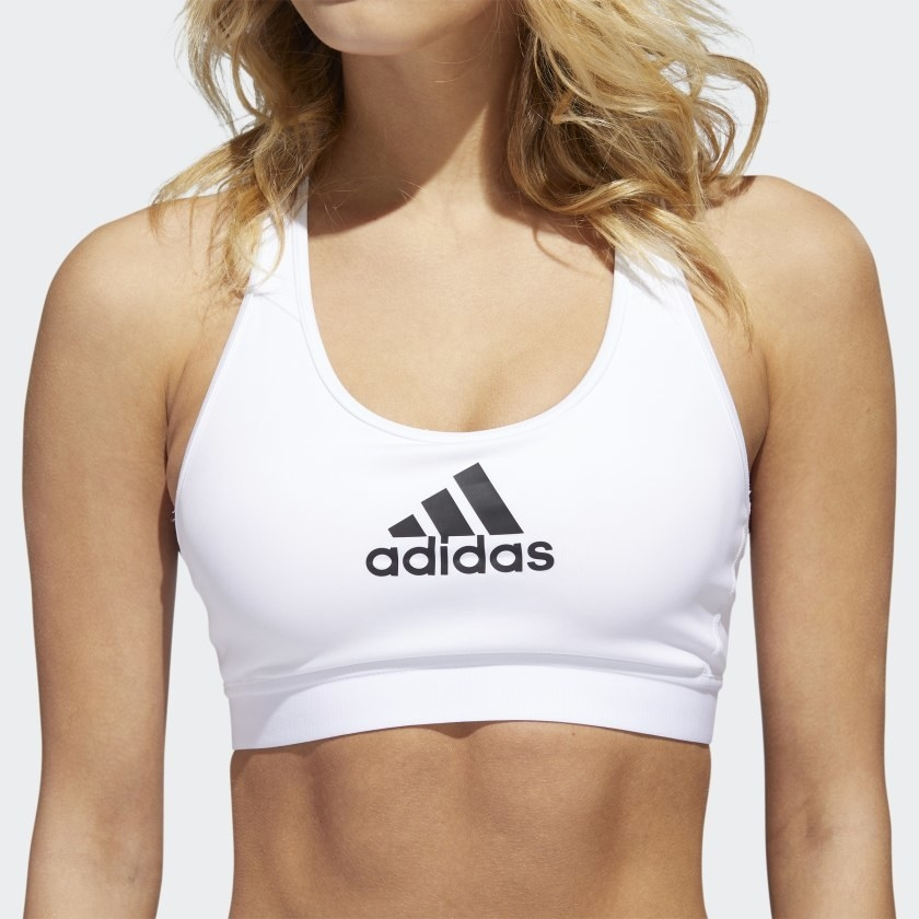 Model wearing white sports bra with black Adidas logo