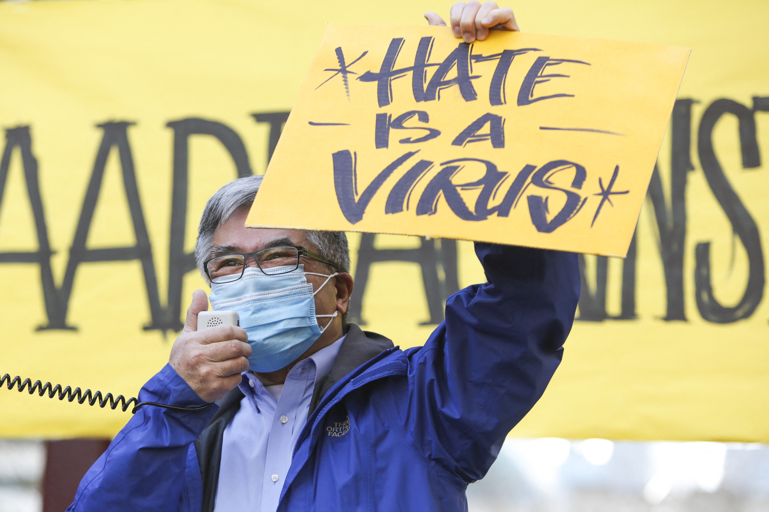 """The former governor of Washington, Asian American Gary Locke, speaks at a rally in Seattle in a medical mask while holding a sign that says, """"Hate is a virus"""""""