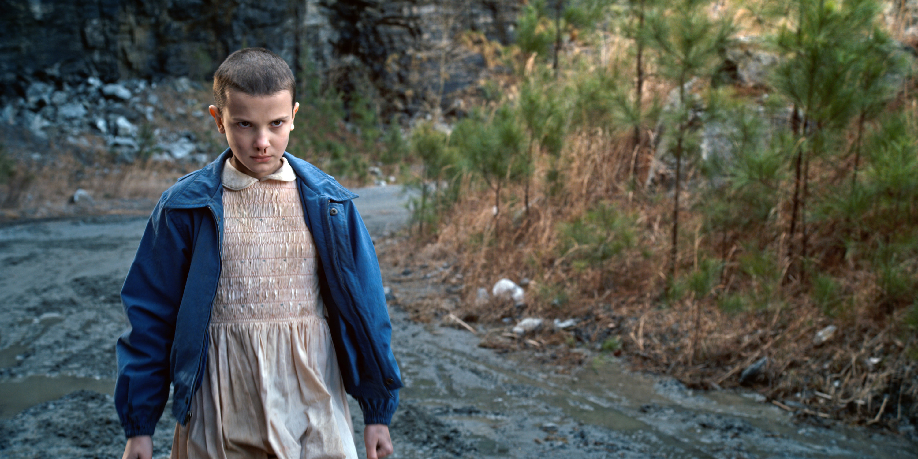 Eleven with a nosebleed walking menacingly down the road in Stranger things