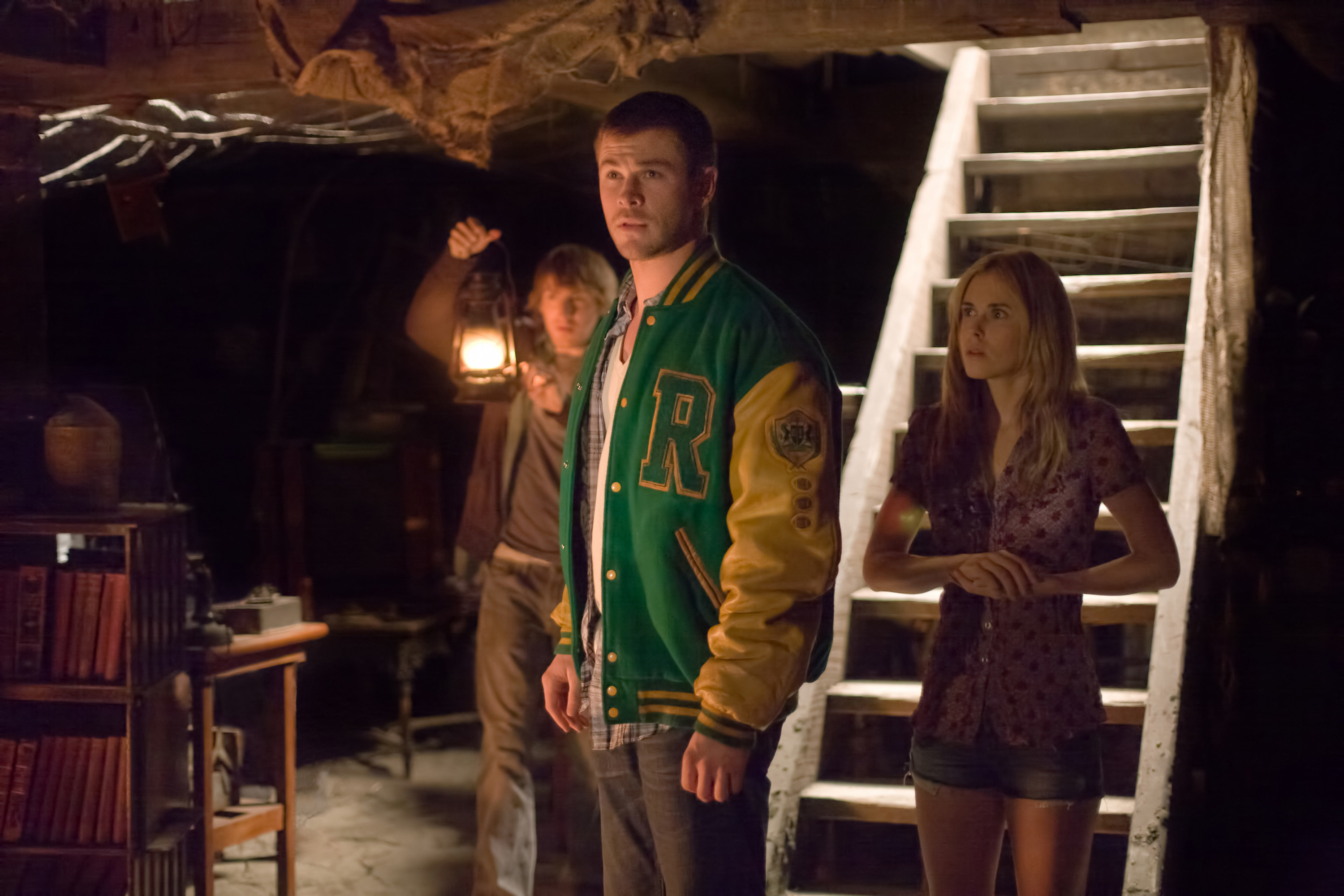Curt standing in a basement in a Letterman jacket in The Cabin In The Woods