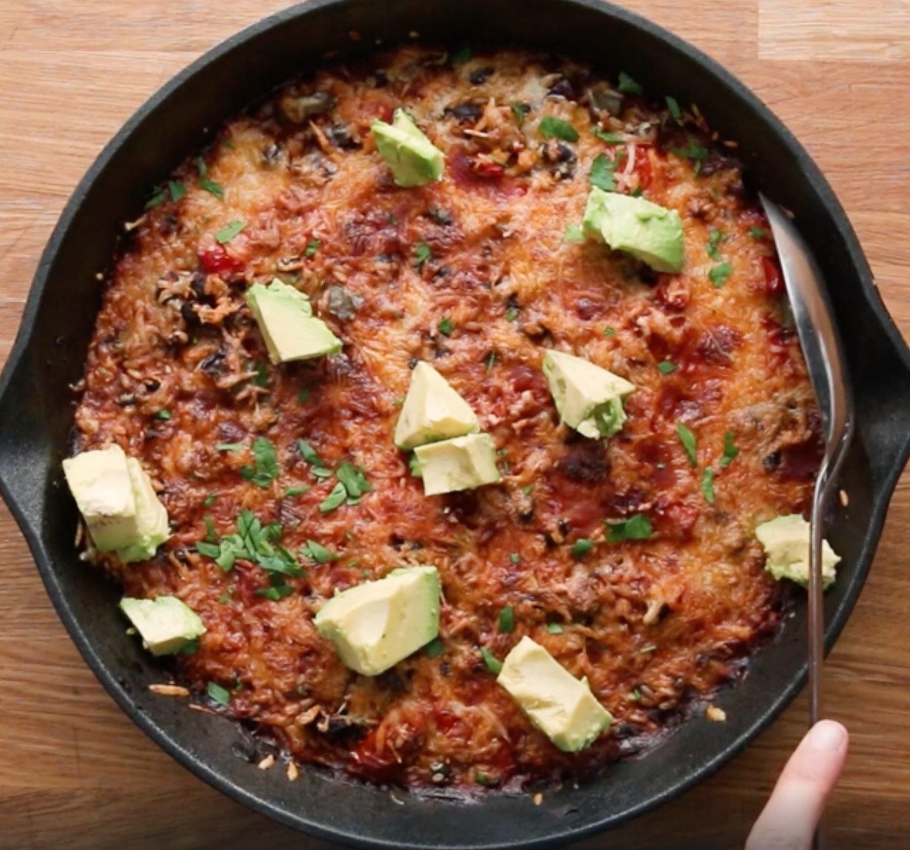 Enchilada rice in pan with fresh avocado