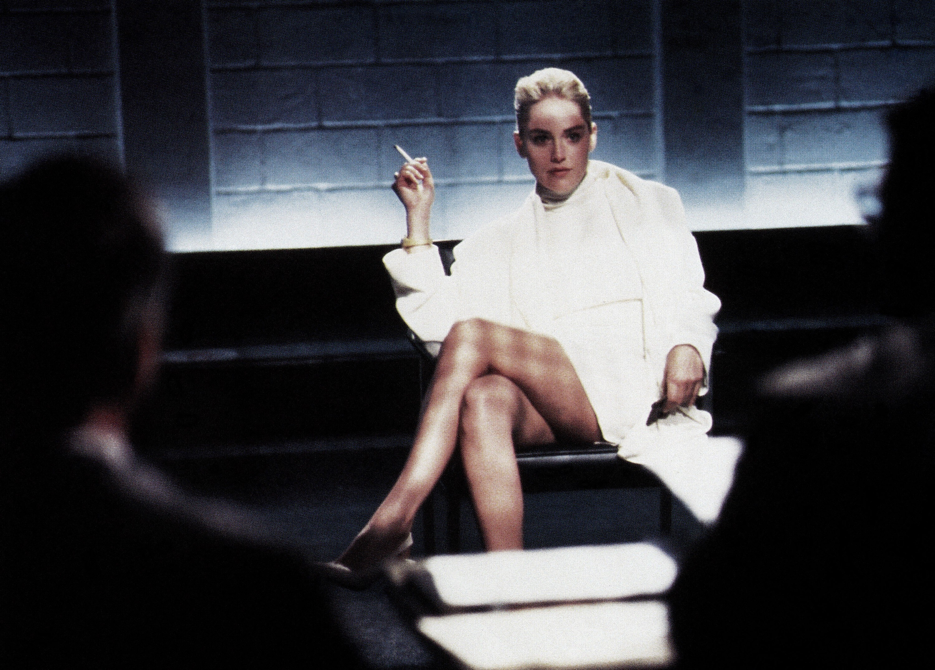 Stone sits with her legs crossed in Basic Instinct