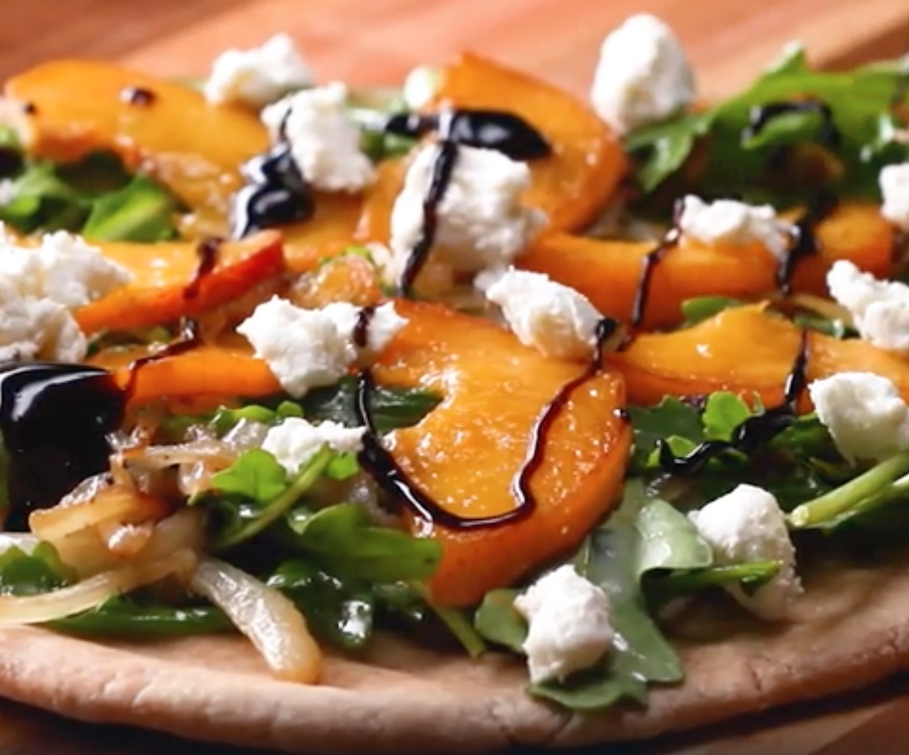 A flatbread pizza with peaches and goat cheese