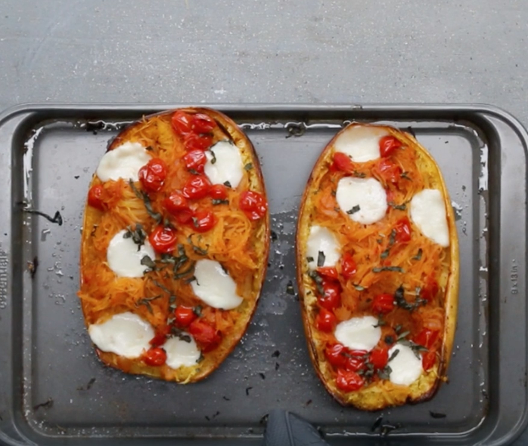 A pan with two roasted spaghetti squashes topped with tomatoes and mozzarella