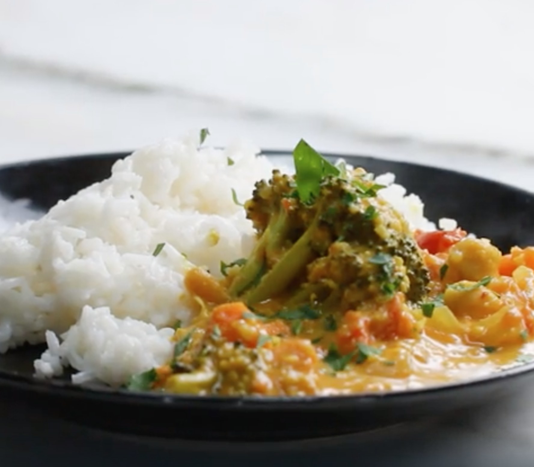 A bowl of coconut veggie curry with white rice