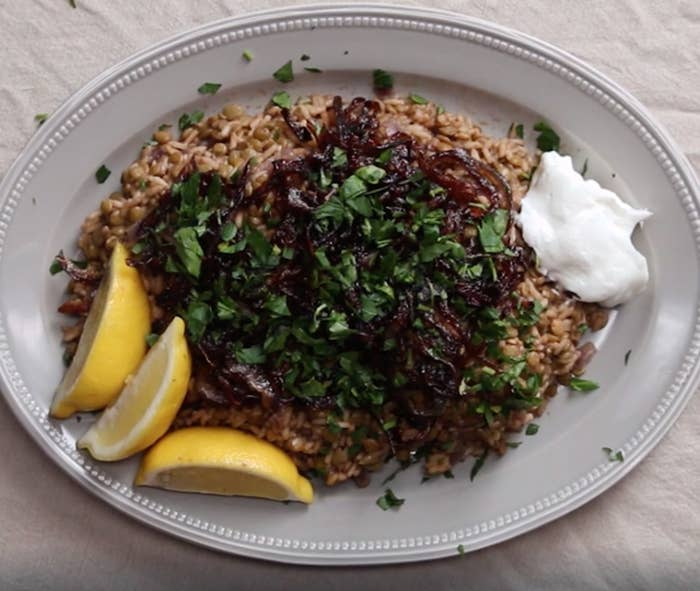 A platter of lentils and rice with caramelized onions, lemon wedges and Greek yogurt