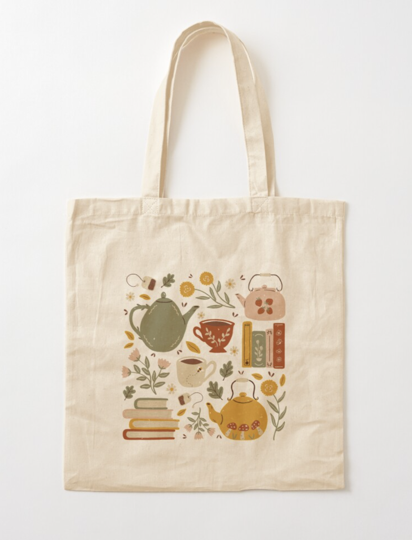 A vintage-style tote bag with whimsical illustration of teapots, teacups, plants, flowers, and books