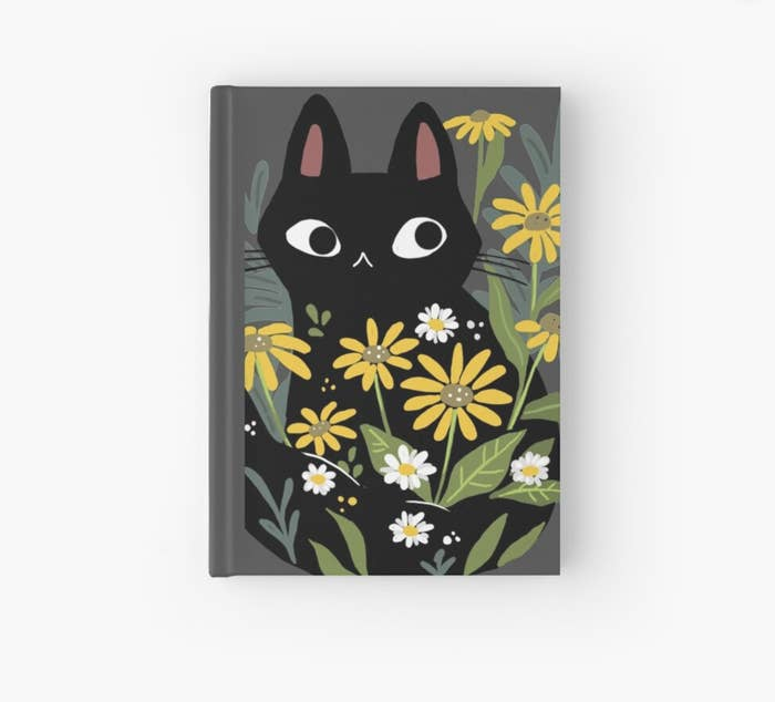 the journal with illustration of big black cartoonish cat with large eyes, surrounded by yellow flowers and daisies