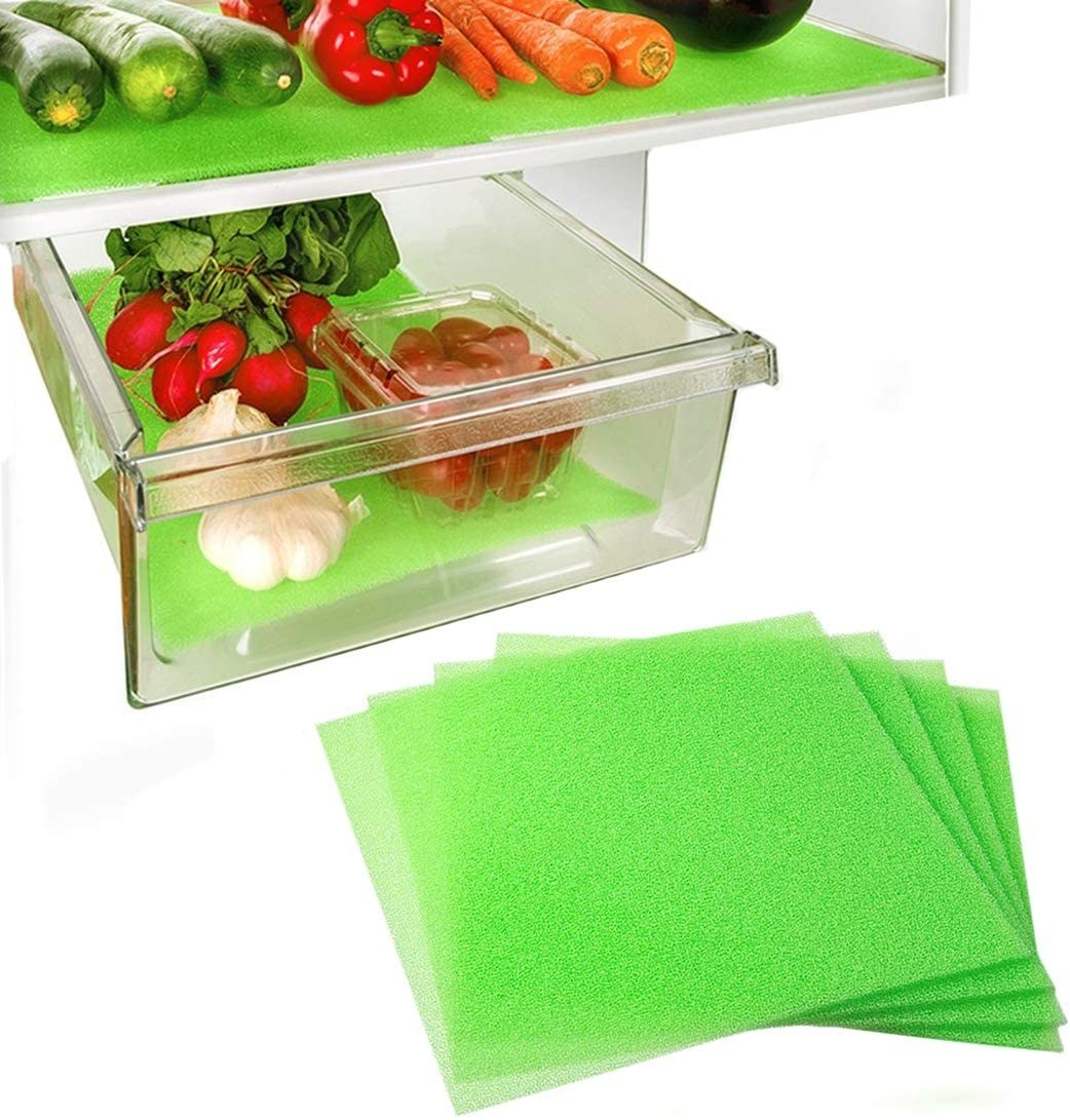 Green liners placed inside crisper drawer with veggies on top