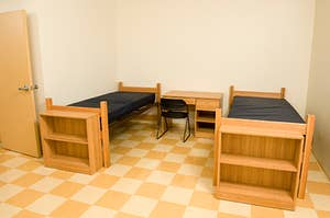 An empty dorm room with two twin beds and a desk with a chair in between