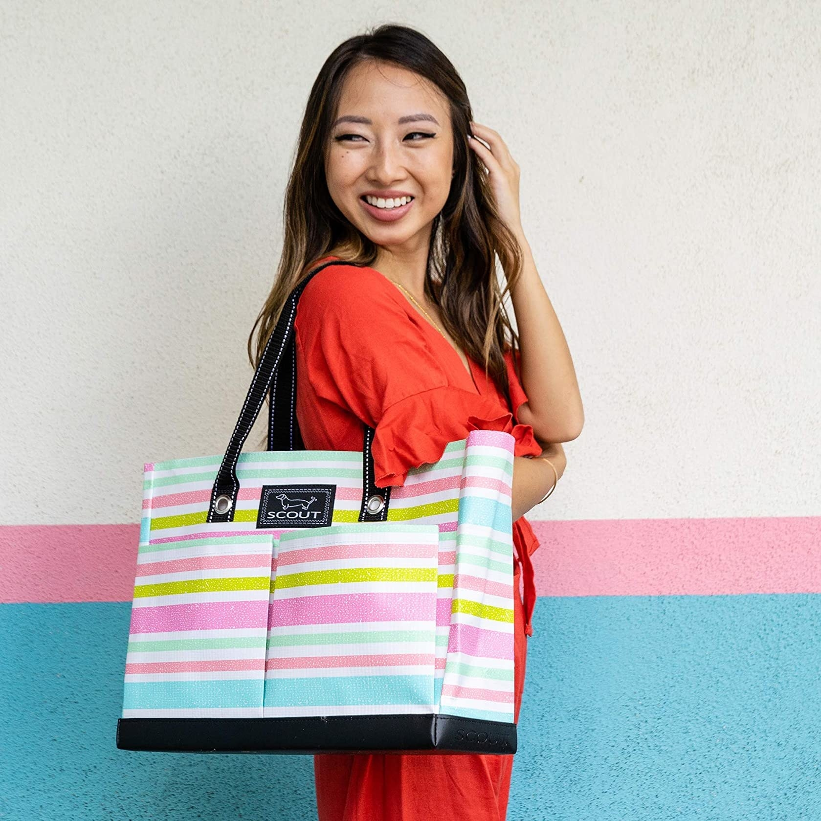 Model wearing the tote in light blue, pink, and gold stripes
