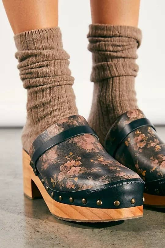 Black leather clogs with wooden base and heels. They have metal studs and a floral pattern on top.