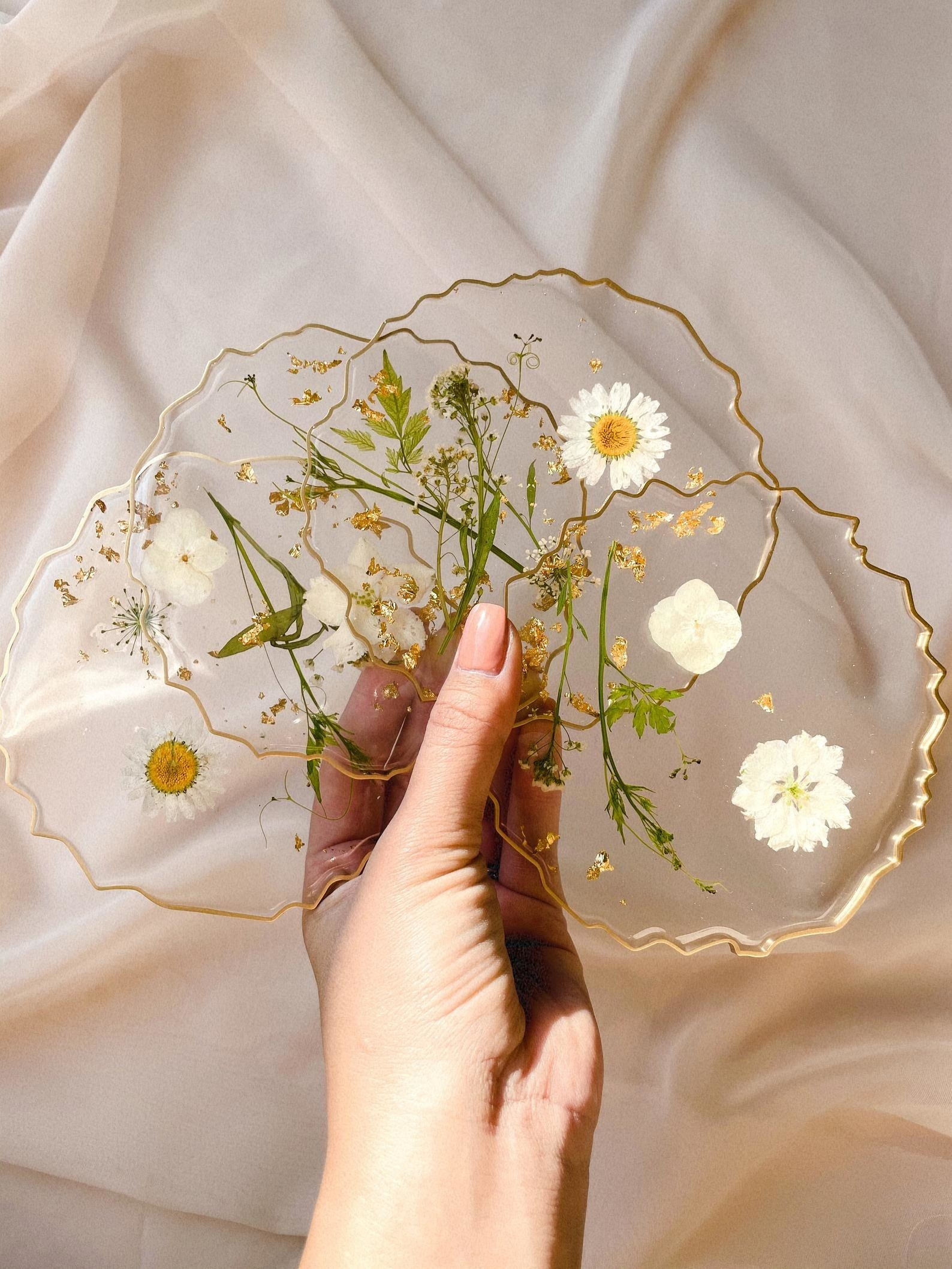 Set of transparent coasters with uneven edged gold rim and white pressed flowers inside
