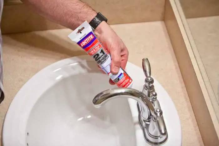 A person placing the sealant on a sink