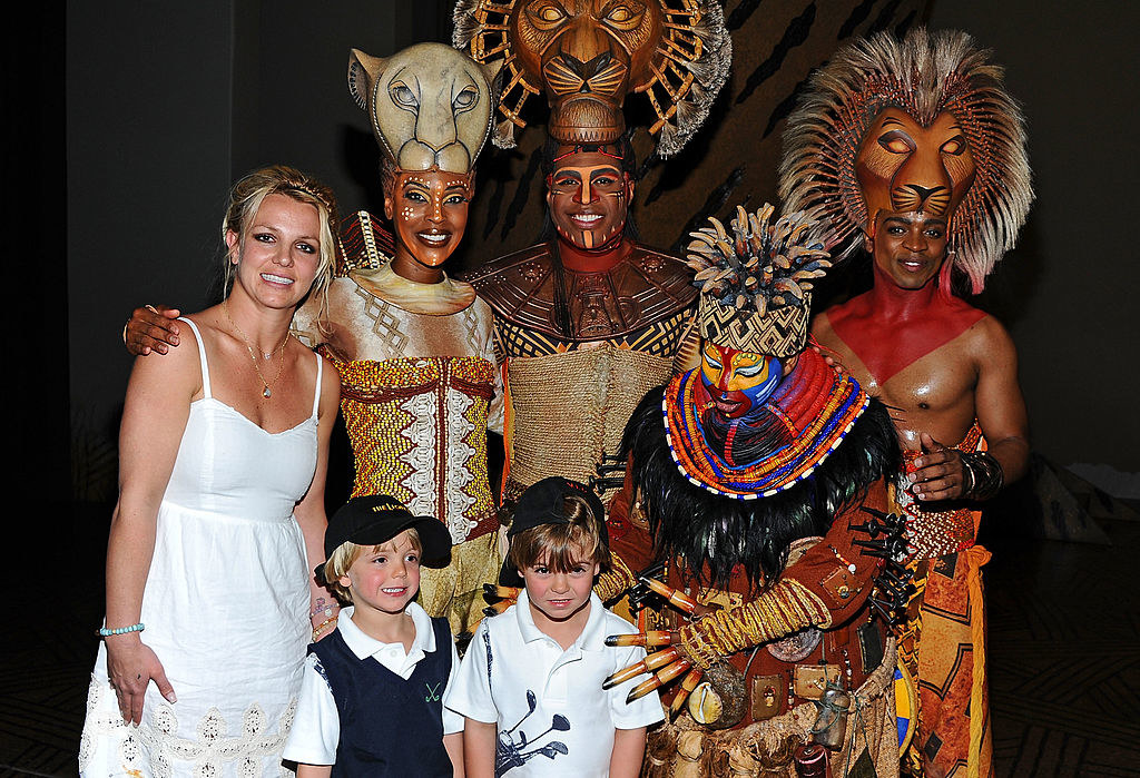 Britney smiling awkwardly as she and her sons pose with the cast