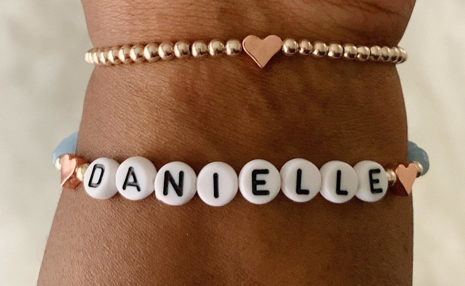 a wrist with a beaded bracelet that spells out danielle