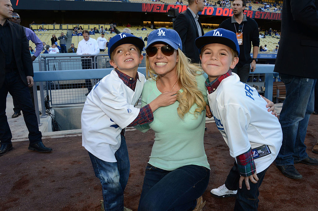 Britney leaning down to pose with her sons who are wearing Dodgers jerseys and baseball caps