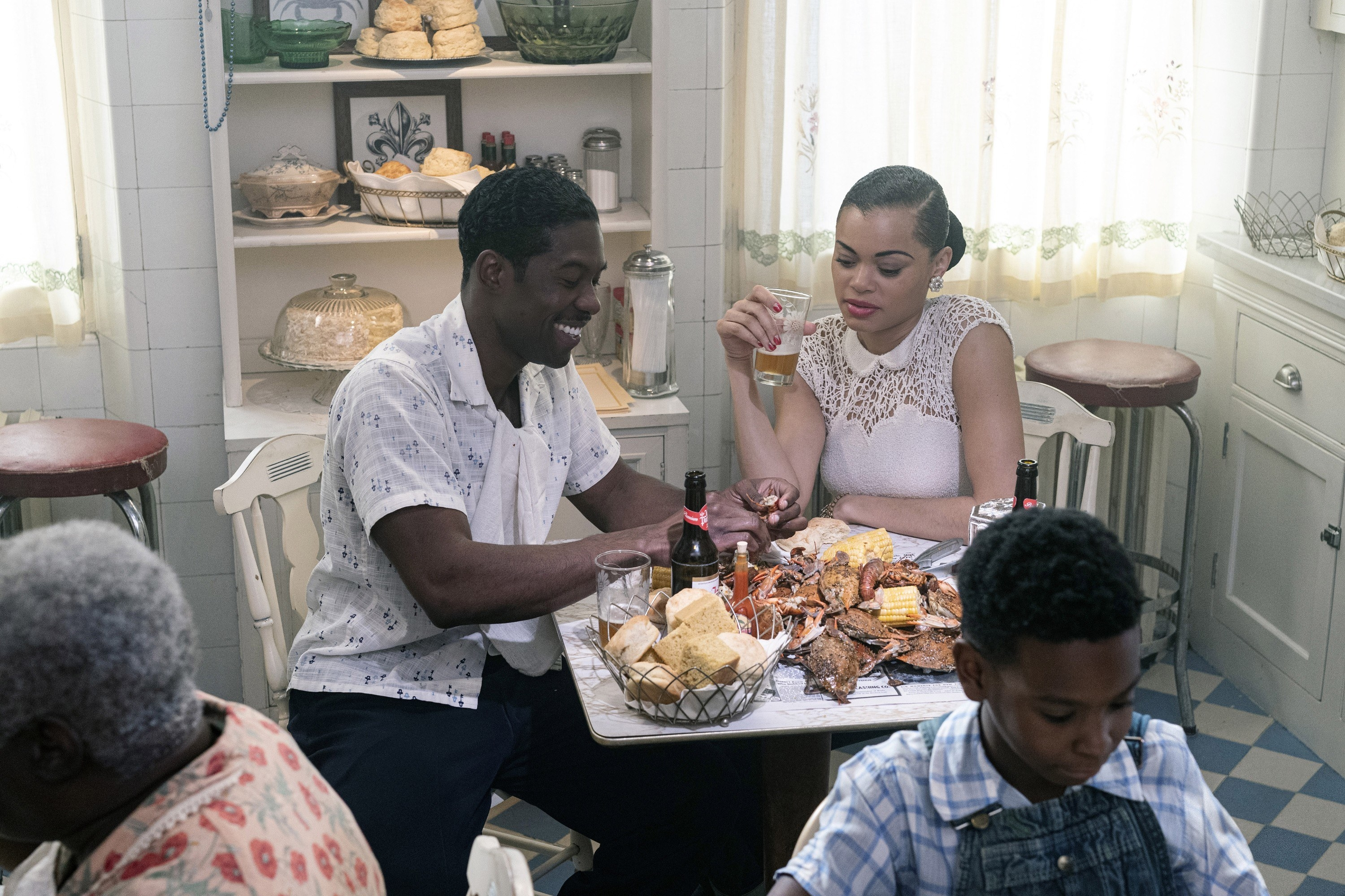 Trevante and Billie eating and drinking at a table in a scene from The United States Vs. Billie Holiday