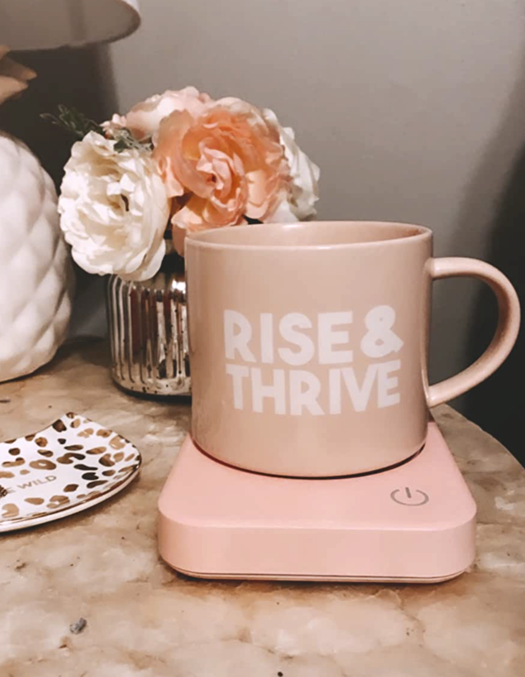 """A pink mug of coffee that says """"Rise & thrive"""" sitting on top of a pink heated small plate"""