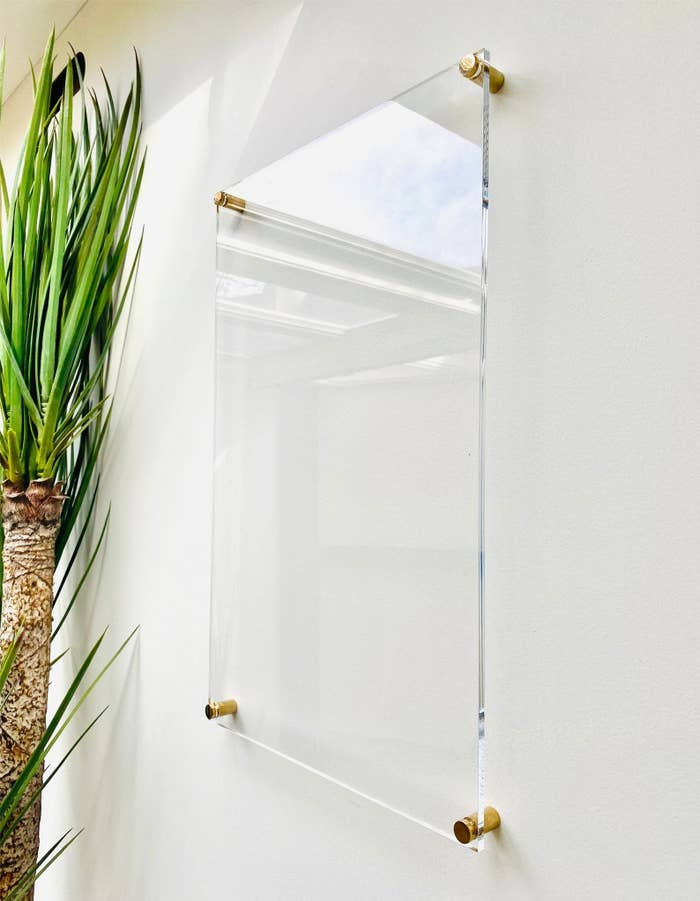 Square transparent whiteboard with four gold knobs installed on a wall