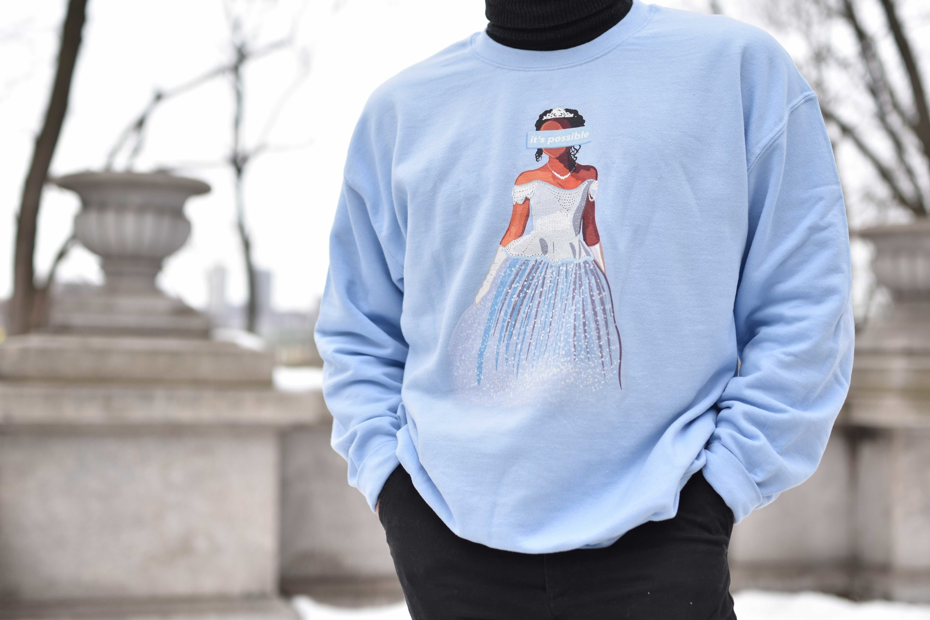 "a model wearing a light blue sweatshirt with an illustration of brandy on it as cinderella with a blue rectangle over her eyes that say ""it's possible"""