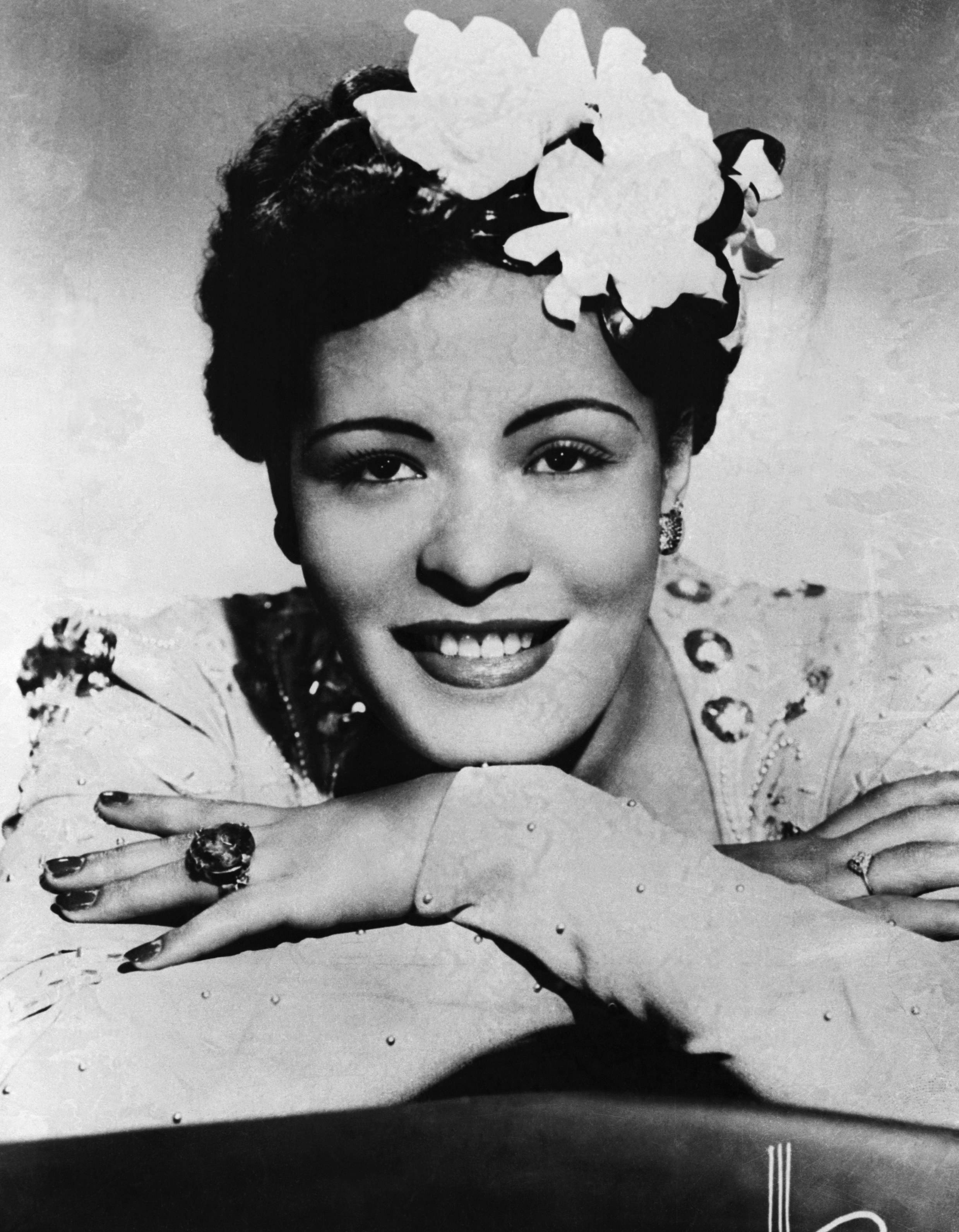 Billie Holiday with flowers in her hair and head resting on her hands