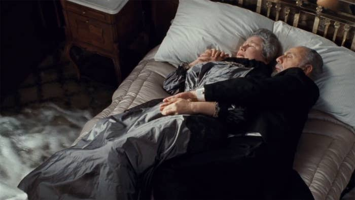 An elderly couple embrace in bed as water rushes into the room around them