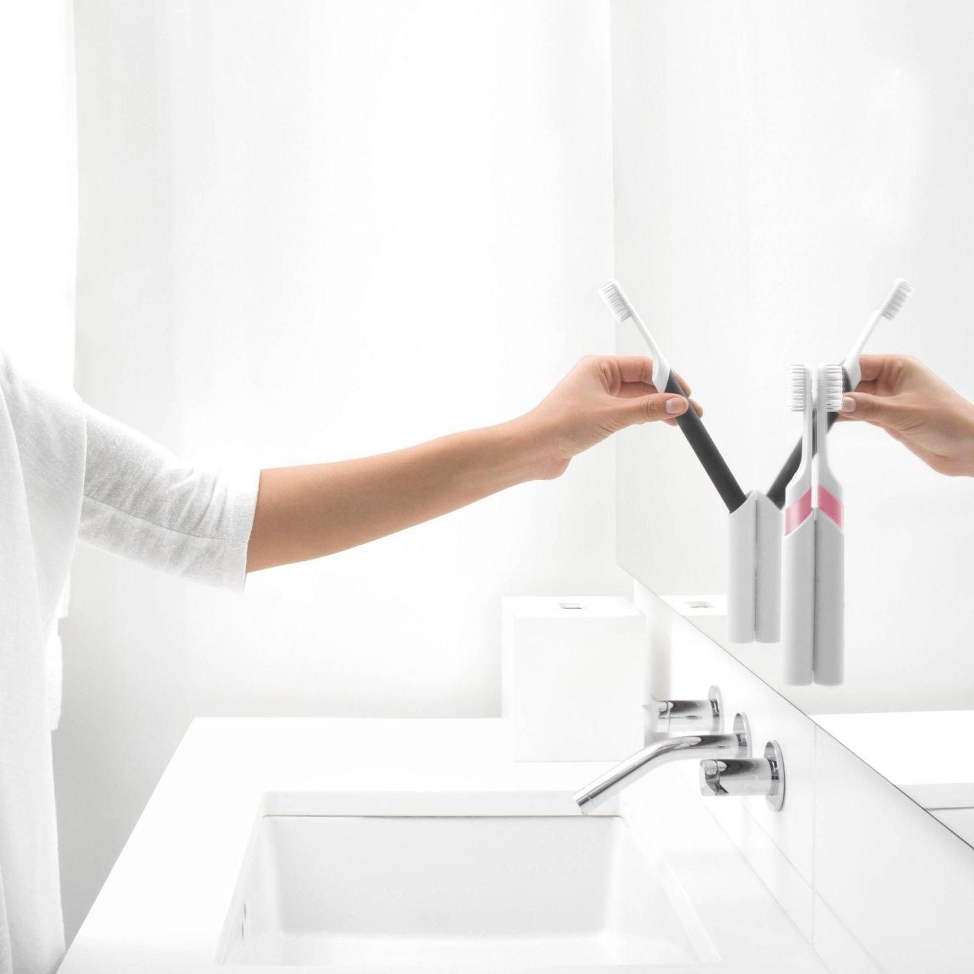 Model putting toothbrush away in bathroom