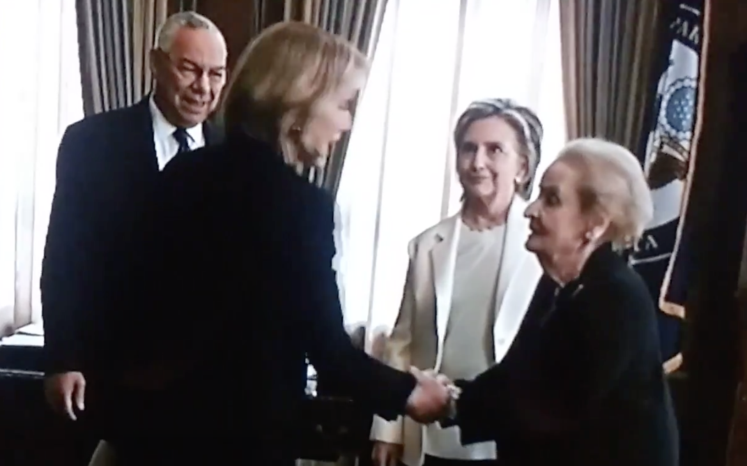 Elizabeth shaking Madeline's hand on the show as Hillary and Colin look on