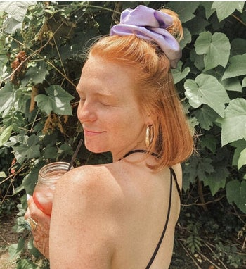 a purple satin scrunchie in a person's straight red hair