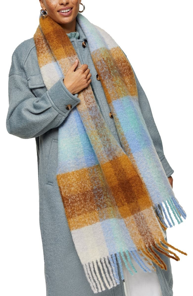model wearing a blue brown and white plaid scarf