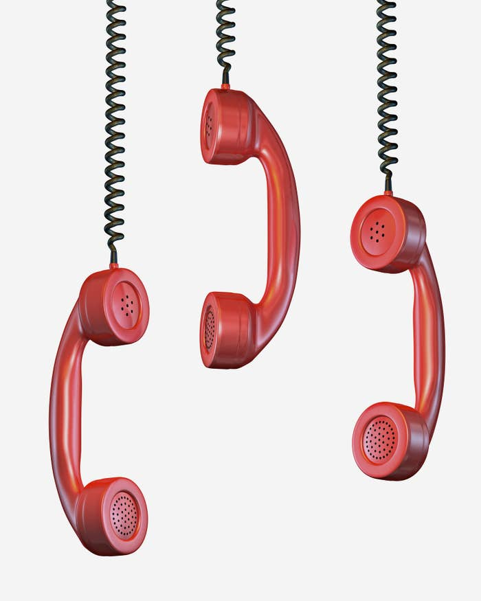 Three red phone receivers hanging in the air