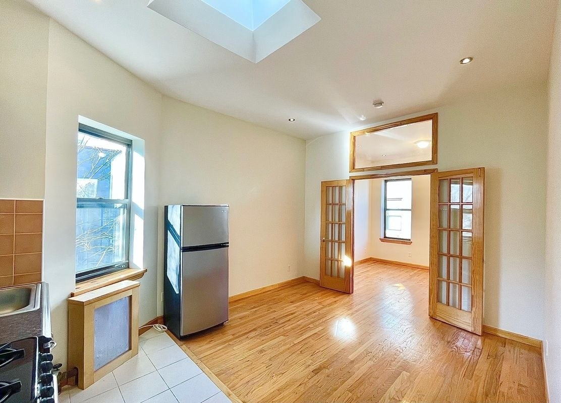 An open concept apartment with a stainless steel fridge, wood floors, gas stove, and double doors leading into another room