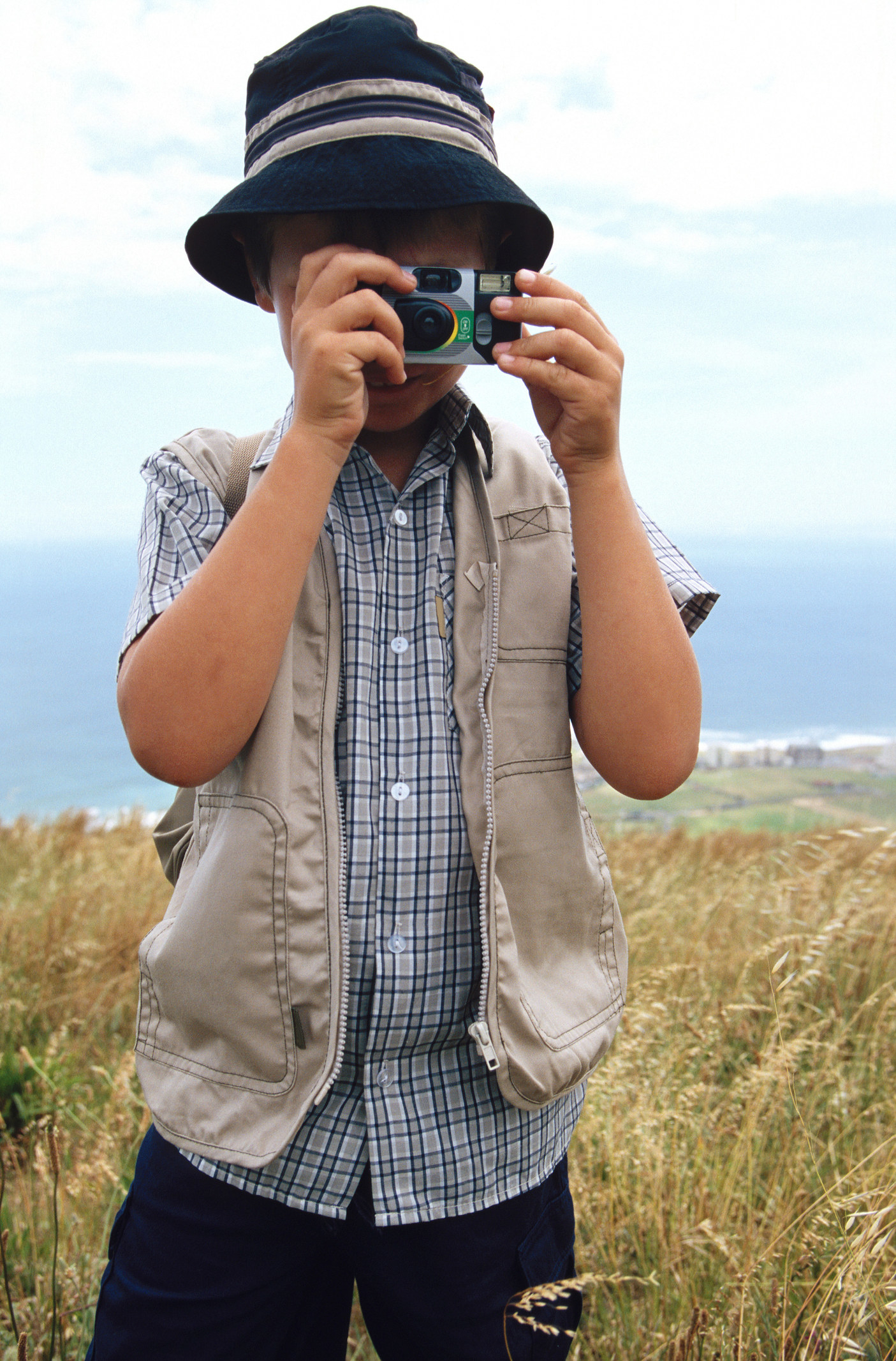 A young boy holding a disposable camera to his face