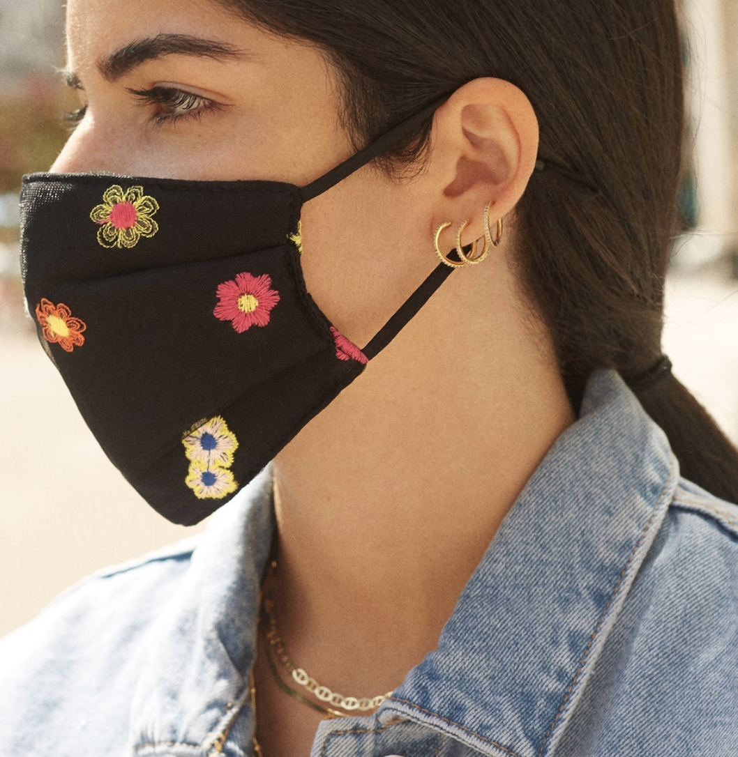 Model in black face mask with flower embroidery