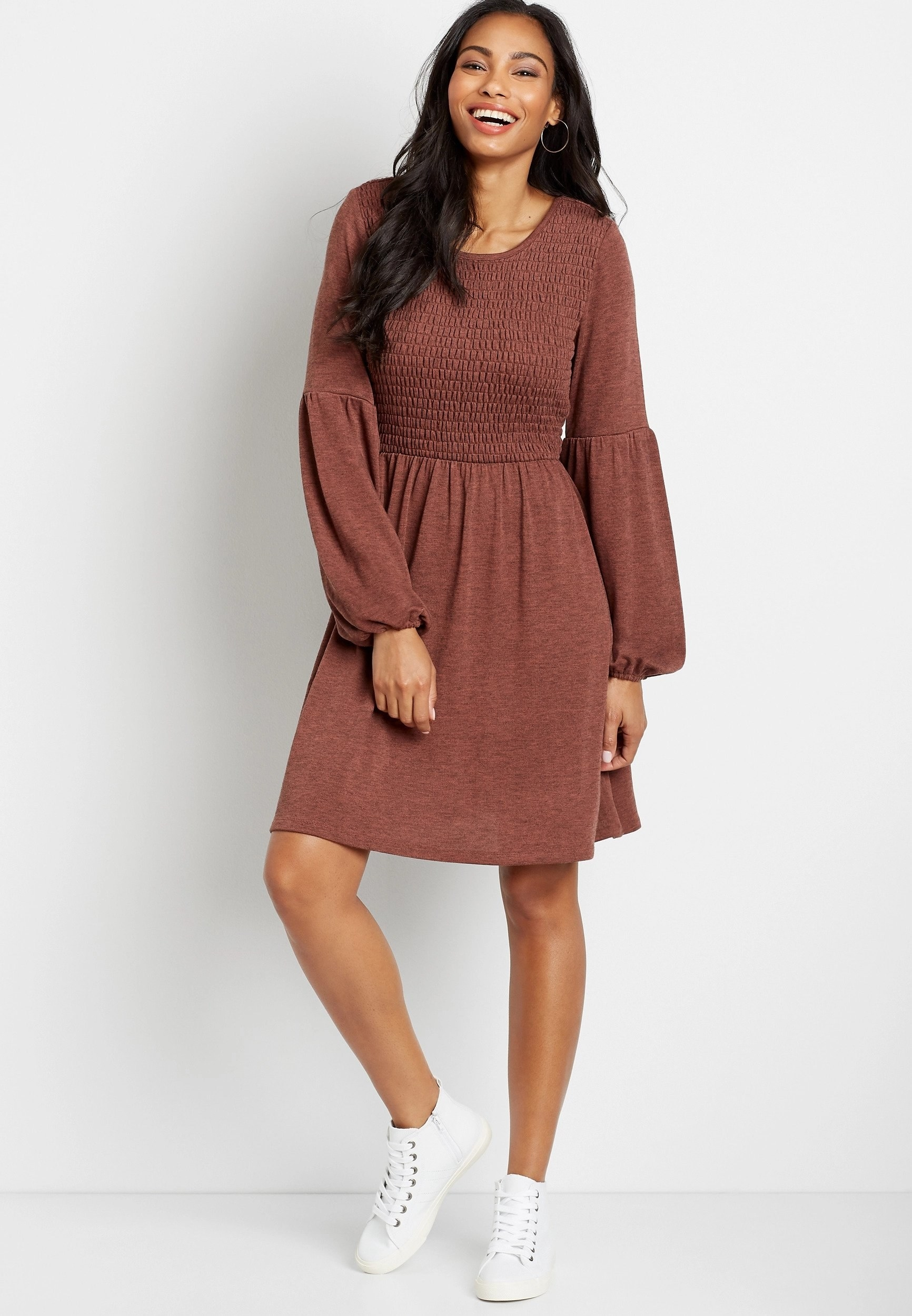 model in red long-sleeve babydoll dress and white sneakers
