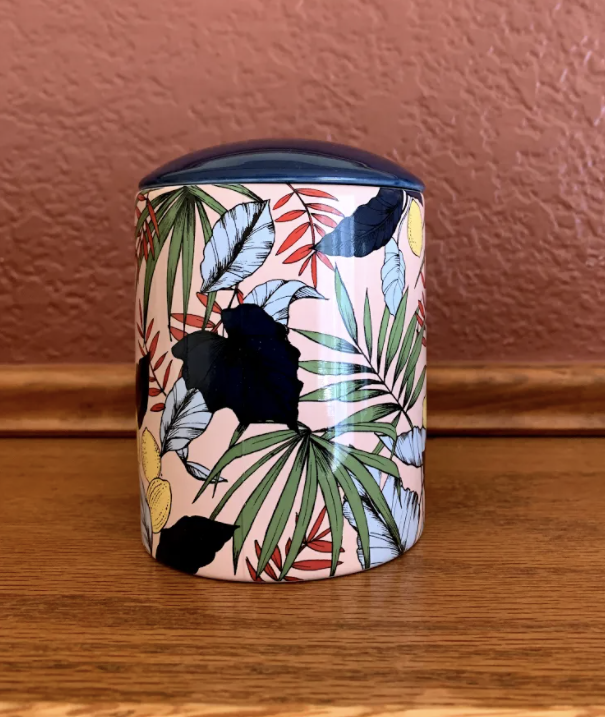 kit's candle in a pink, palm, and floral pattern container