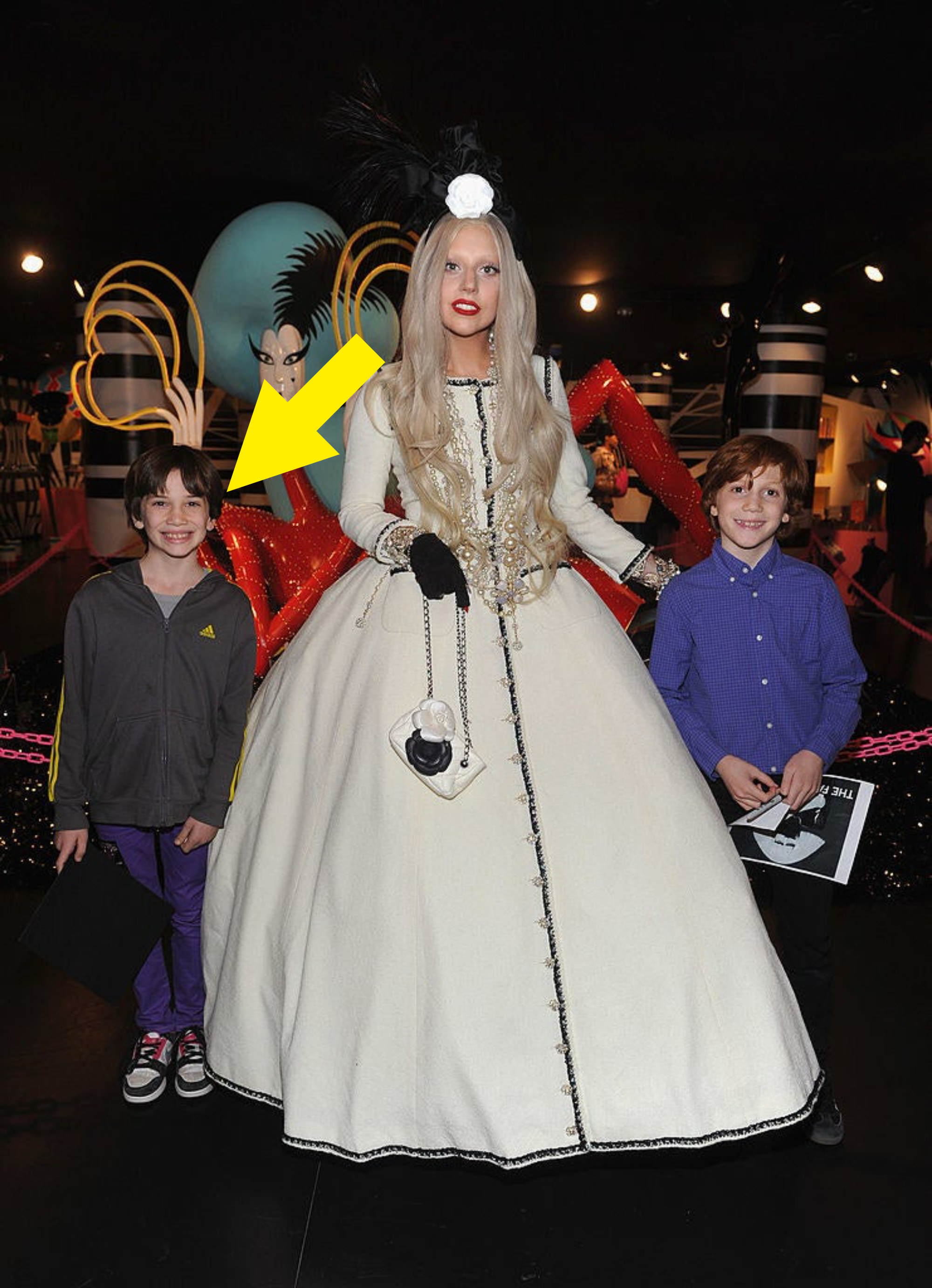 Lady Gaga is wearing a ballgown and matching floral headpiece as she poses for a photo with two young children, one of whom has an arrow pointing at him identifying him as Bill Gates