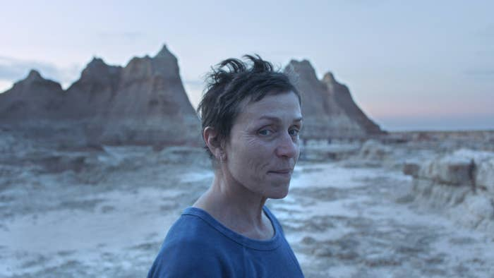 Frances McDormand as Fern in Nomadland standing in front of rock pinnacles at sunset
