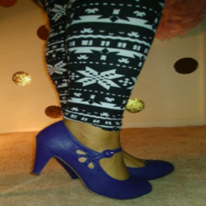 A reviewer wearing the navy heels with petal-like cutouts near the strap