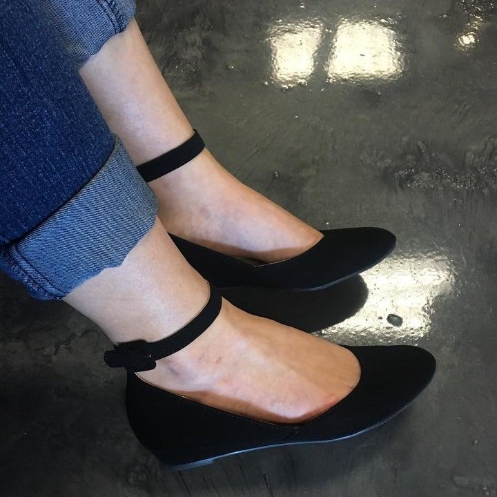 A reviewer wearing the shoes in black