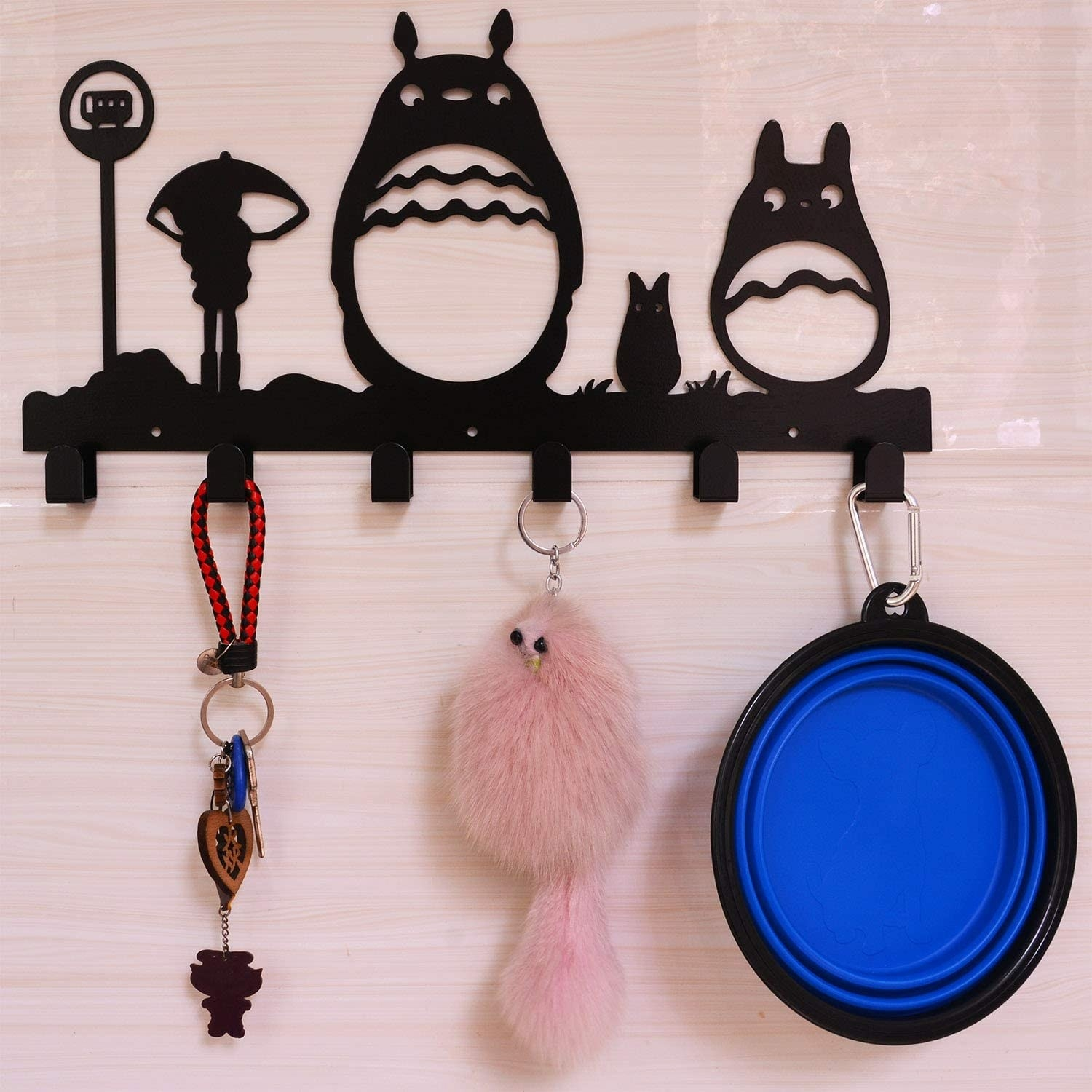 """the """"Totoro"""" coat rack hanging on a wall with keys and keychains hanging on the hooks"""