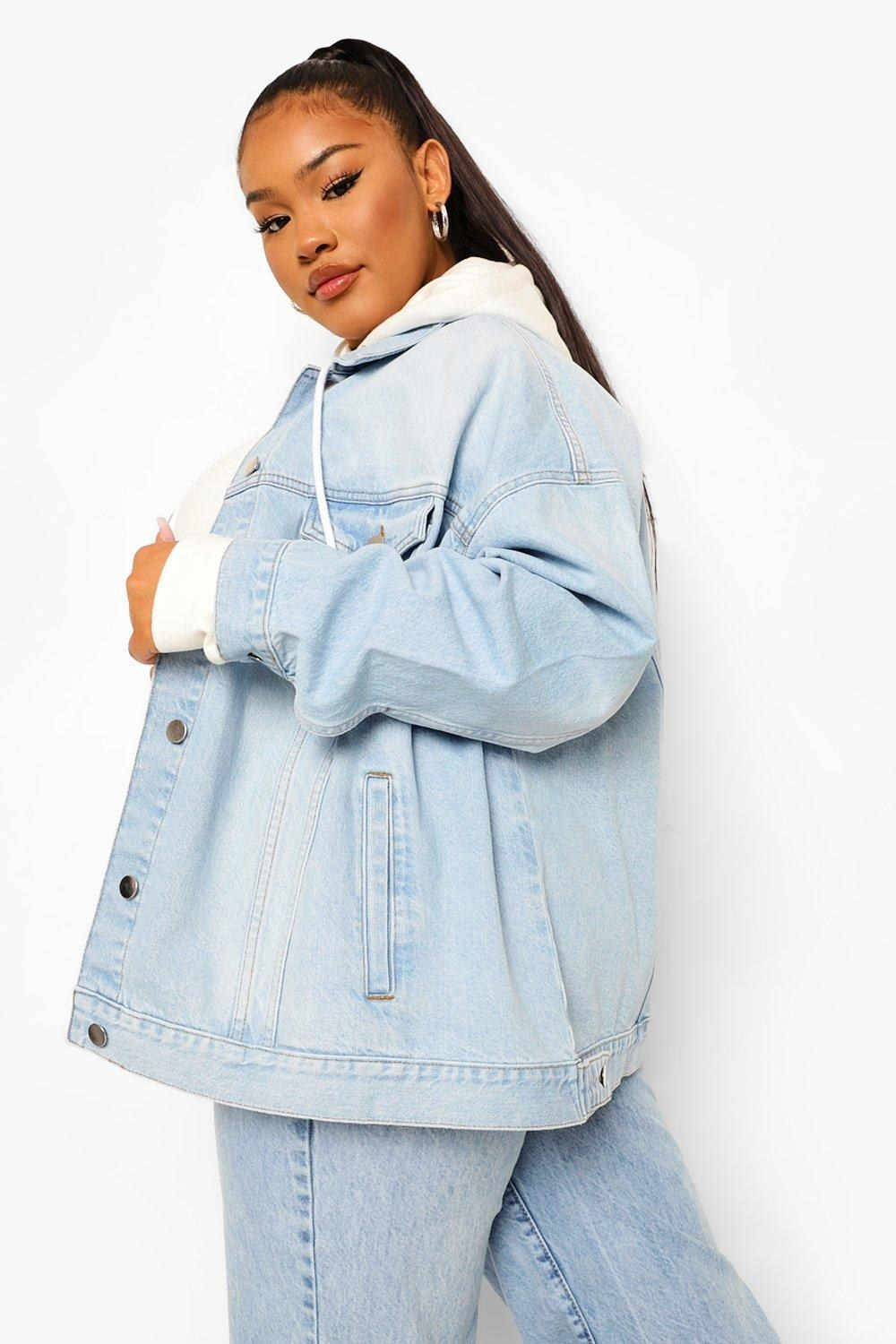 model in light blue denim jacket, white hoodie, and jeans