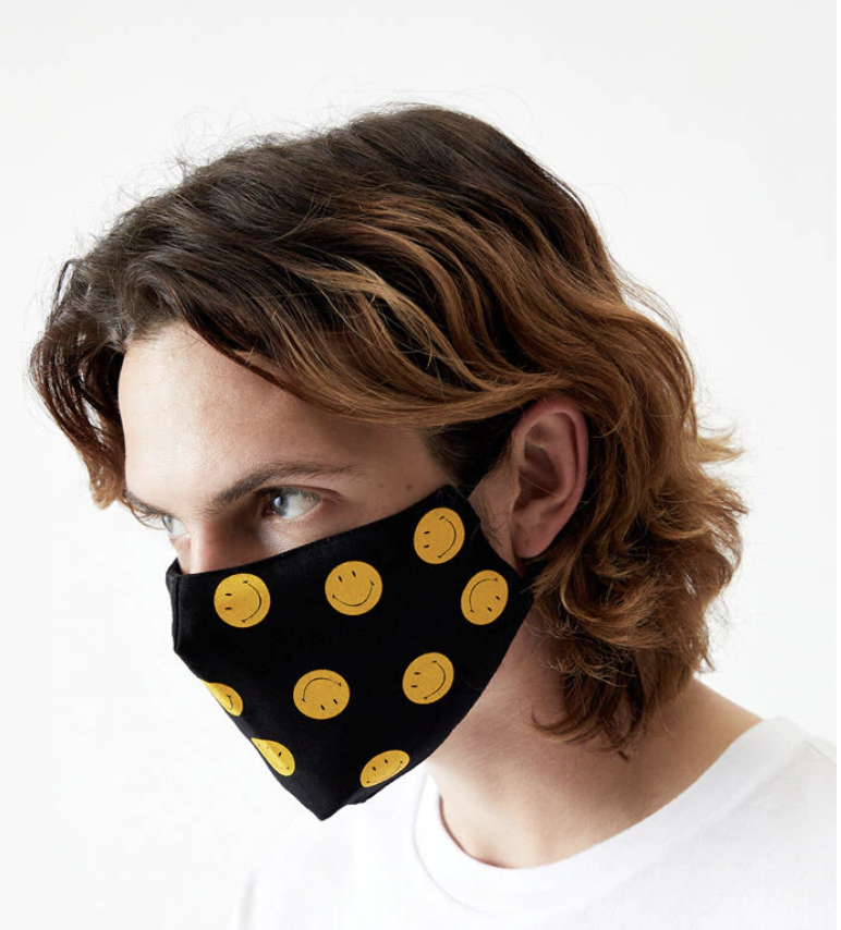 Model in black face mask with yellow smiley faces on it